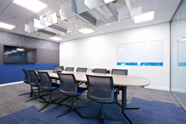 Boardroom with hanging acoustic baffle and acoustic wall and branded drywipe